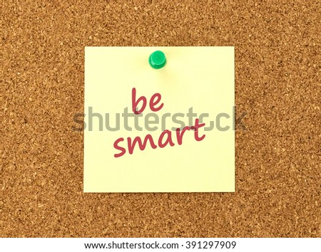 The phrase Be Smart in red text on a yellow sticky note posted to a cork notice board.