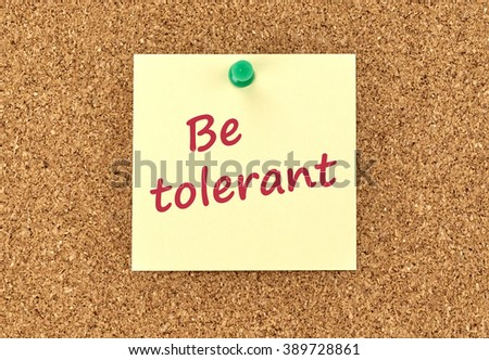 The phrase Be Tolerant in red text on a yellow sticky note posted to a cork notice board.