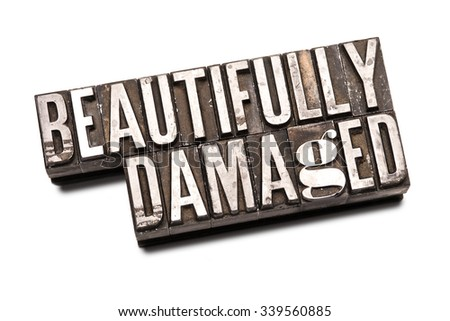 "The phrase ""Beautifully Damaged"" in letterpress type. Cross processed, narrow focus."