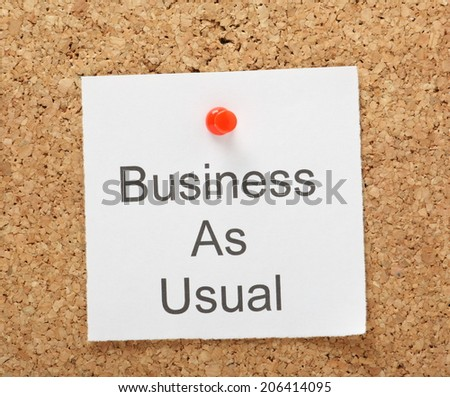 The phrase Business as Usual typed on a piece of note paper and pinned to a cork notice board - stock photo