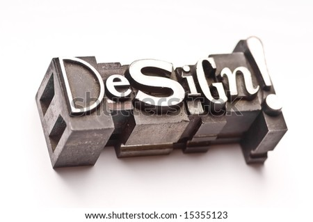 "The phrase ""Design!"" done in random letterpress type on a white paper background. - stock photo"