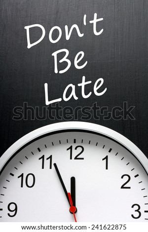 The phrase Don't Be Late written on a blackboard above a clock face with the hands pointing towards midnight or twelve o'clock. - stock photo