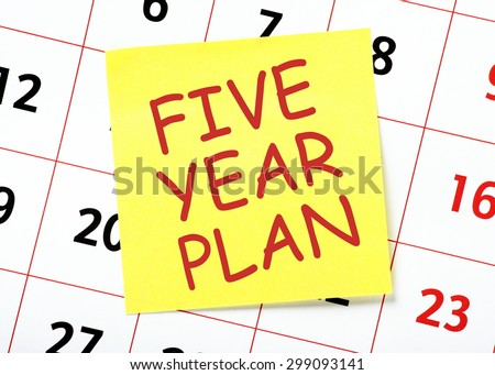 The phrase Five Year Plan on a yellow sticky note posted on a calendar or planner page as a reminder - stock photo