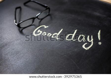 "the phrase ""Good day"" on the blackboard with chalk"