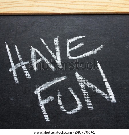 The phrase Have Fun written by hand on a slate blackboard using white chalk