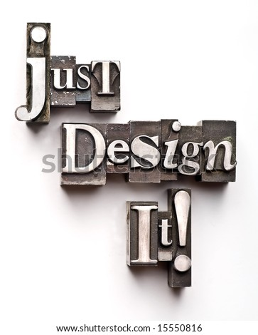 "The phrase ""Just Design It!"" done in random letterpress type on a white paper background. - stock photo"