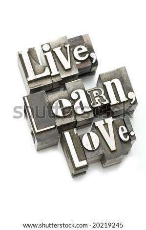 The phrase Live, Learn, Love photographed using vintage letterpress type with shallow focus.
