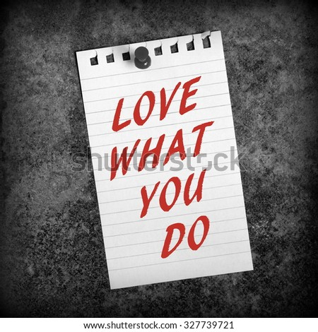 The phrase Love What You Do in red text on a piece of lined paper pinned to a background processed in black and white for effect - stock photo