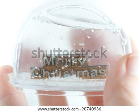 "The phrase ""Merry Christmas"" in snow globe on white background - stock photo"