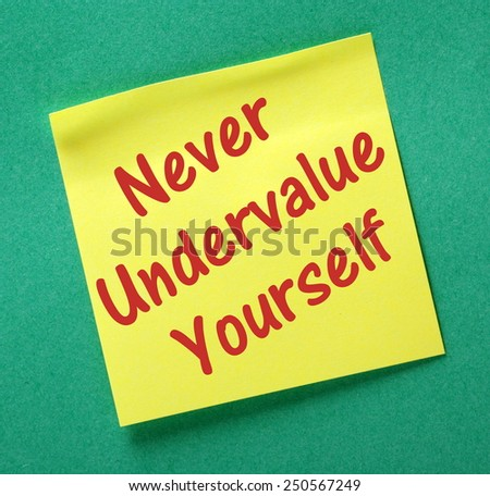 The phrase Never Undervalue Yourself written on a yellow sticky note posted on a green background - stock photo