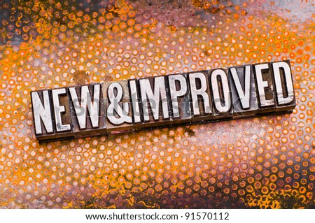 "The phrase ""New & Improved"" in letterpress type. Cross processed, narrow focus. - stock photo"