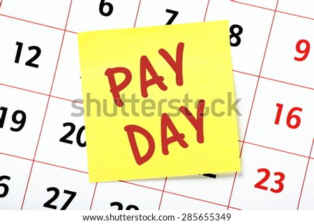 The phrase Pay Day in red text on a yellow sticky note posted on the page from a calendar as a reminder - stock photo