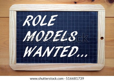 The phrase Role Models Wanted in white text on a used blackboard as a call out for people who can mentor and set standards of behavior
