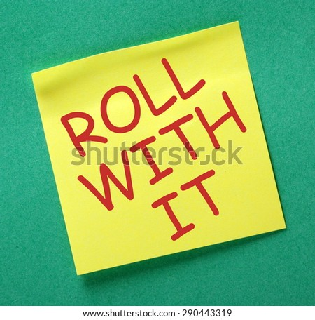 The phrase Roll With It in red text on a yellow sticky note posted on a green notice board - stock photo