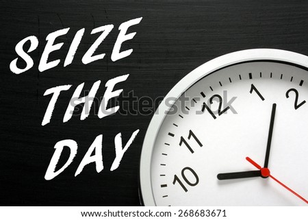 The phrase Seize The Day in white text on a blackboard next to a modern wall clock displaying the time - stock photo