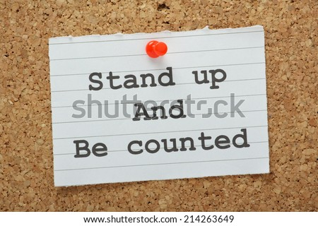 The phrase Stand Up and Be Counted typed on a piece of land paper and pinned to a cork notice board as a reminder - stock photo