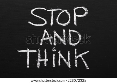 The phrase Stop and Think written on a blackboard as a reminder to take time out and work through our options before taking action - stock photo