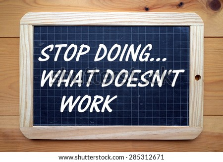 The phrase Stop Doing What Doesn't Work in white text on a blackboard - stock photo
