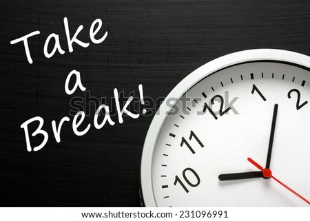 The phrase Take A Break written on a blackboard next to a modern office clock. A reminder to find time in your busy schedule to relax - stock photo