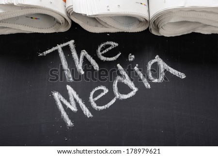 The phrase The Media written on a blackboard next to rolled up newspapers - stock photo