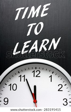 The phrase Time To Learn in white text on a blackboard above a modern wall clock - stock photo