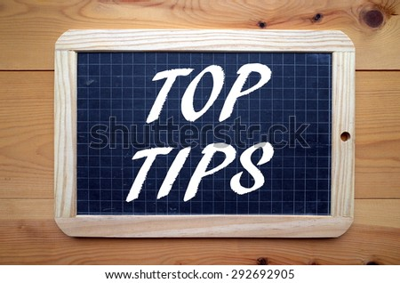 The phrase Top Tips in white text on a slate blackboard - stock photo