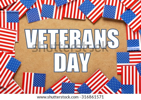 The phrase Veterans Day in block letters on a paper background surrounded by a border of flags of the United States of America  - stock photo