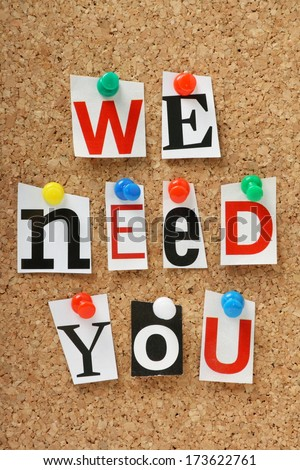 The phrase we need you in cut out magazine letters pinned to a cork notice board - stock photo
