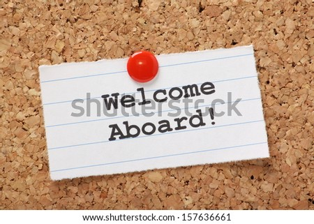 The phrase Welcome Aboard! typed onto a scrap of lined paper and pinned to a cork notice board. A phrase used to welcome a new employee or team member. - stock photo
