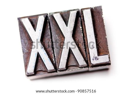 "The phrase ""XXL"" in letterpress type. Cross processed, narrow focus. - stock photo"