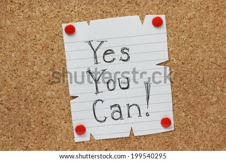 The phrase Yes You Can written by hand on a piece of paper pinned to a cork notice board