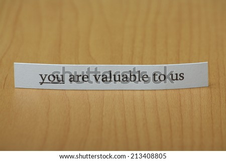 The phrase you are valuable to us typed on a strip of paper and left standing on a wooden desktop - stock photo