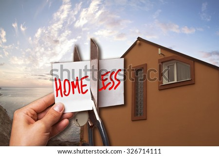 "The picture house on the beach, in the foreground hand scissors cut card ""homeless."" The concept of making the right choice. The picture for the sale of real estate and construction. - stock photo"