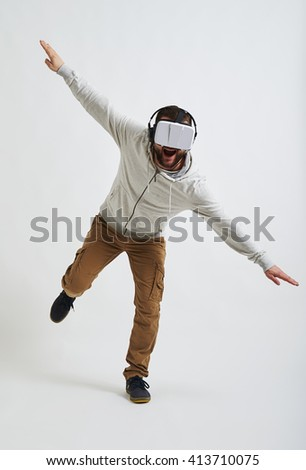 The picture in 3d reality glasses seems so real to the young man that he is trying to balance on one leg  - stock photo