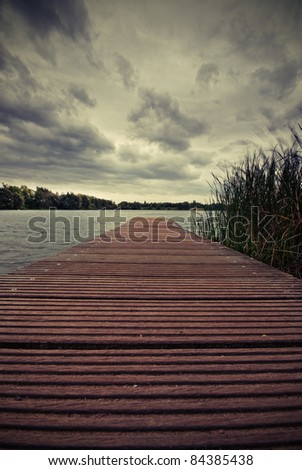 The picture shows a lake and a cloudy sky. - stock photo