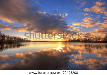 The picture shows a lake during sunset. - stock photo