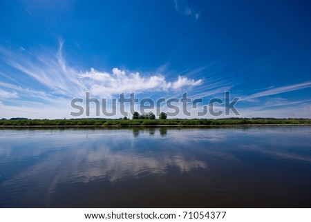 The picture shows a river and a blue sky. - stock photo