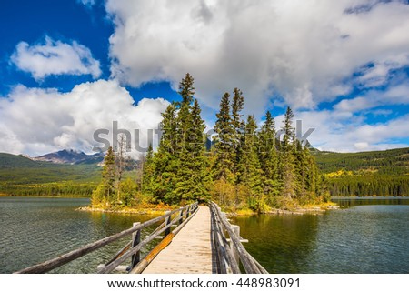 The picturesque little island in the middle of the lake. For it is a wooden bridge. Jasper National Park, Pyramid Lake. Cold sunny morning - stock photo