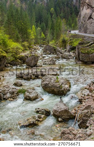 The picturesque mountain river with boulders at the foot of the cliff to the road. It is in the Carpathian Mountains, Romania, Transylvania. - stock photo
