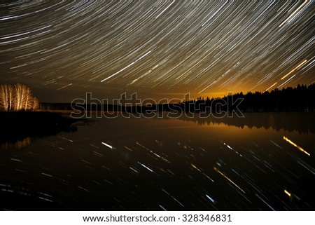 The picturesque night view of the lake, forest and stars in the form of tracks, reflecting in the water