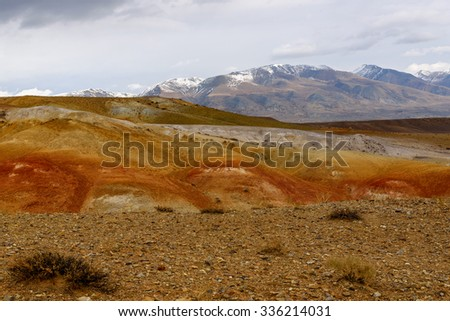 The picturesque steppe desert landscape with multicolored mountains, cracks in the ground and sparse vegetation on the background of other mountains and cloudy sky in autumn - stock photo