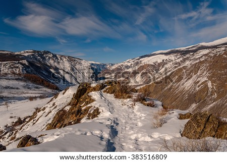 The picturesque top view on the mountains covered with snow, cliffs and the valley between the mountains on background of blue sky and clouds in winter - stock photo