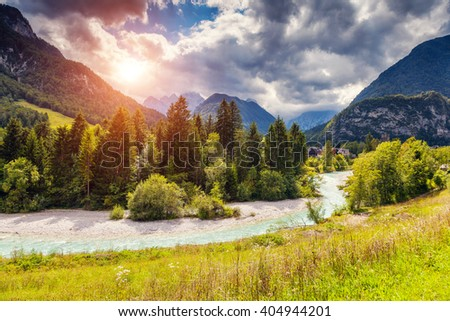 The picturesque view of the mountains that glow under sunlight. River in a green field. Dramatic unusual scene. Location place: Triglav national park, Julian Alps. Slovenia, Europe. Beauty world. - stock photo