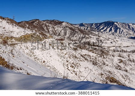 The picturesque winter top view on the mountains covered with snow, the valley between the mountains, the trees and asphalt winding road on a background of blue sky - stock photo