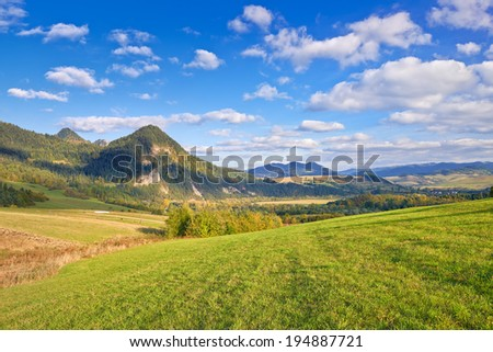 The Pieniny Mountains landscape, Carpathians, Poland. Daylight scenery with trees, meadows, mountains and clouds on the blue sky. - stock photo