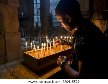 The pilgrims lit candles at the Church of the Holy Sepulchre in Jerusalem, Israel - stock photo