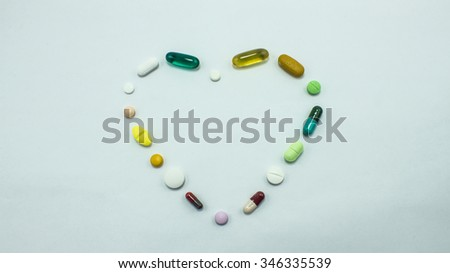 The pill capsules out of package on the white background - stock photo