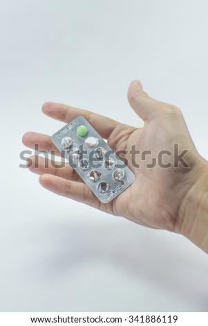 The pill package in hand on thewhite background