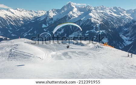 The pilot lands on a paraplane with a mountain-skiing slope of Penken - Mayrhofen, Austria - stock photo