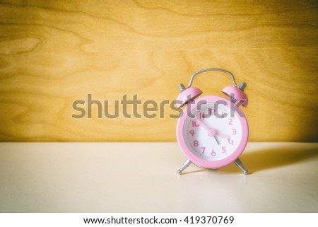 the pink analog alarm clock with the wooden background in vintage style - stock photo